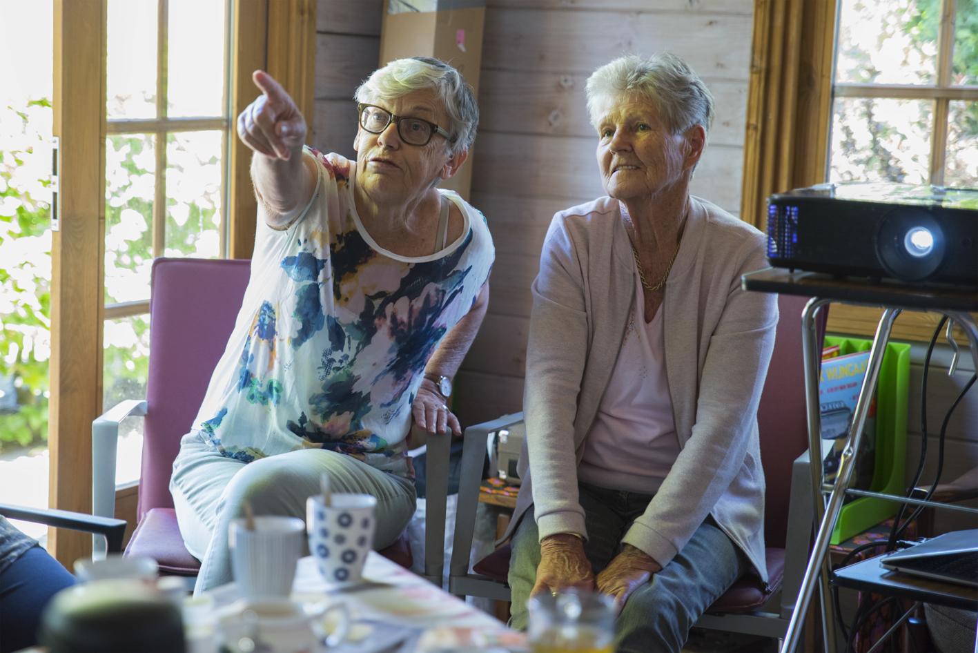 foto van twee oudere dames die tijdens een kunst in de zorg kijksessie van Schitterend Beeld actief deelnemen aan deze dagactiviteit op Ontmoetingscentrum Zorgtuinderij Pieter van Foreest